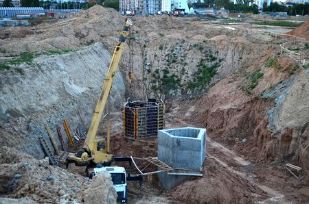 Crane operation in the pit, laying or replacement of underground storm sewer pipes at the construction site. Installation of water main, sanitary sewer and storm drain systems. Utility Infrastructure