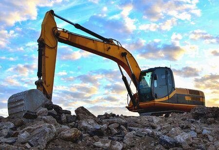 Ładunki koparki z kamienia i gruzu do przetworzenia na cement lub beton do prac budowlanych i ponownego wykorzystania. Koparka w kamieniołomie. Rozwiń glazurę lub piasek i bloki skalne. Nieostrość, przyciemniane
