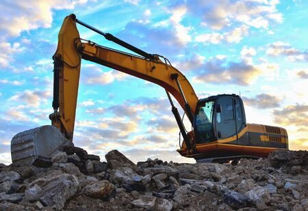 Baggerladungen von Stein und Schutt zur Verarbeitung zu Zement oder Beton für Bauarbeiten und Wiederverwendung. Bagger im Steinbruch. Entwickeln Sie den Kies oder Sand und Felsblöcke. Weichzeichner, getönt