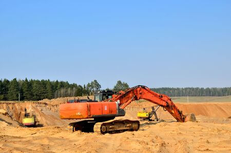 Excavator on the top of an open industrial sand pit where mining operations are carried out
