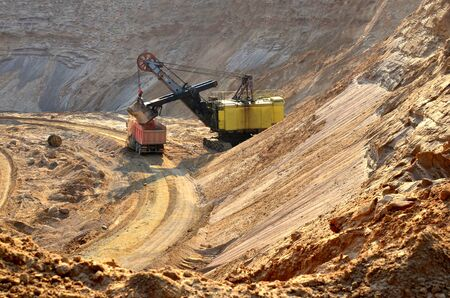 Excavator loading sand to the heavy dump truck at opencast. Biggest digger working in quarry. Largest tracked machine with electric shovel.  Processing of loose material in mining quarry. Drill, breaking, processing plant, crushing and screening Archivio Fotografico