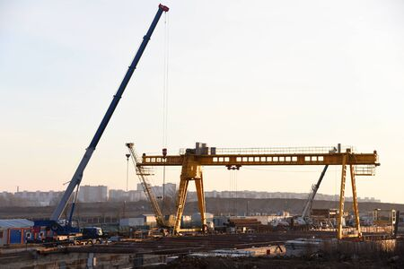 Mobile auto cranes and gantry crane working at construction site. Digging a pit for the building of an underground tunnel of the metro line. Subway construction project, Minsk, Belarus, Aerodromnaya Stock Photo