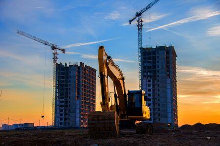 Grande pelle sur chenilles sur un chantier de construction sur fond coucher de soleil. La pelle rétrocaveuse creuse le sol pour la fondation, pose des tuyaux d'égout pluvial. Installation de réseaux d'aqueduc. Réparation de routes