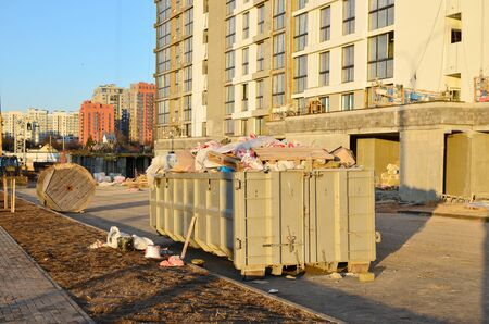 Metal tanks and capacities for storage and transportation of garbage. Metal trash cans and containers for MSW on construction site. Skip for dumping renovation waste.