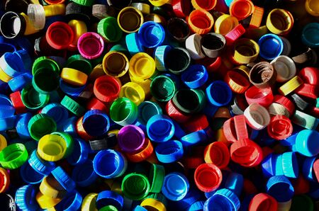 Plastic bottle caps background. Cap material is recyclable.Remove lids from plastic bottles before recycling them. Recycling collection and processing plastic bottle caps