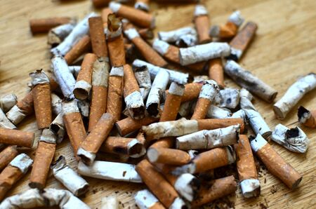 A lot of burnt cigarette butts with some ash.