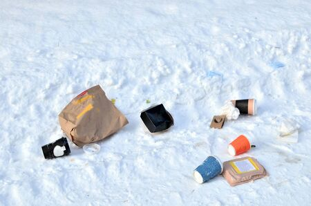 Scattered garbage in the city on the road in the snow. Packages and containers from the fast food meal thrown out on the street by people.