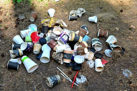 14.05.2019, Minsk, Belarus: Discarded coffee cups and fast food packaging in the forest on ground. People left behind trash. The concept of pollution of nature and the environment, background, texture