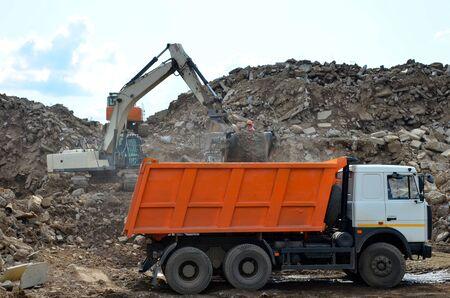 L'escavatore carica i rifiuti edili in un trituratore mobile in cemento armato per la frantumazione, il riciclaggio dei rifiuti misti da costruzione. Riciclaggio di calcestruzzo rotto in discarica industriale. Impianto di vagliatura Archivio Fotografico