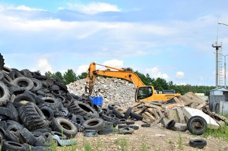 Industrial landfill for recycling used rubber tires and old concrete structures. Excavator with hydraulic shears for crushing and cutting reinforced concrete slabs. Secondary crushed stone - Image Reklamní fotografie