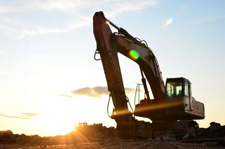 Large tracked excavator digs the ground for the foundation and construction of a new building in the city. Road repair, asphalt replacement, laying or replacement of underground sewer pipes - Image