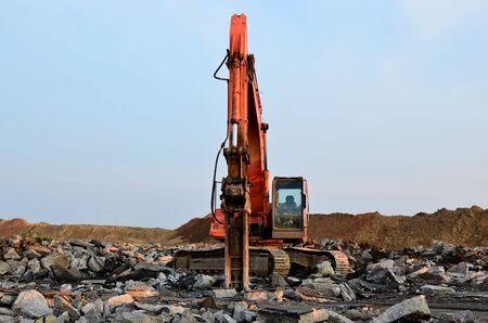 Crawler excavator with hydraulic hammer for the destruction of concrete and hard rock at the construction site. Salvaging and recycling building and construction materials, concrete demolition waste