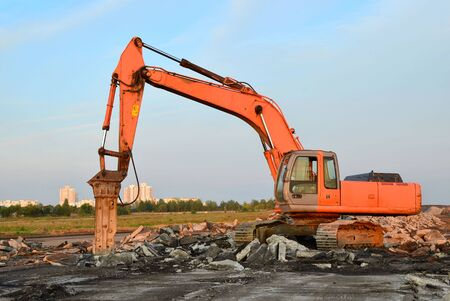 Raupenbagger mit Hydraulikhammer zur Zerstörung von Beton und Hartgestein auf der Baustelle Standard-Bild