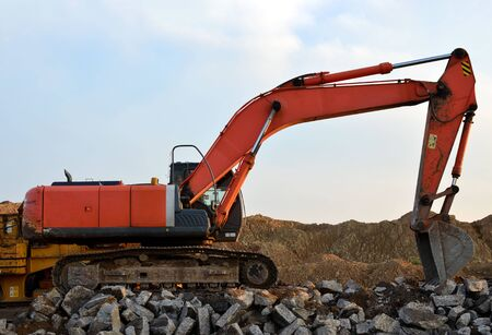 Heavy excavator working at gravel quarry unloads old concrete stones for crushing and recycling to gravel or cement. Special heavy construction equipment for road construction.