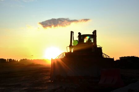 Silhouetted bulldozer on the background of the rays of the sun at sunset at a construction site. Land clearing, grading, pool excavation, utility trenching, utility trenching and foundation digging Zdjęcie Seryjne
