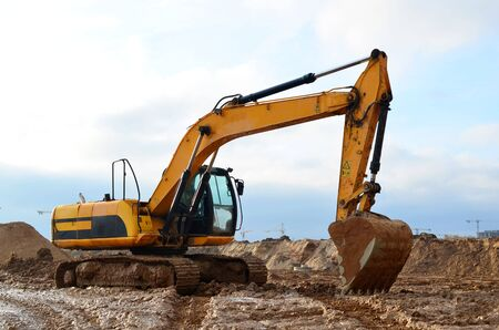 Tracked excavator working at a construction site during laying or replacement of underground storm sewer pipes. Installation of water main, sanitary sewer, storm drain systems - Image