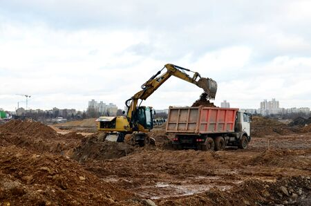08.11.2019 Minsk, Belarus: Wheeled excavator CATERPILLAR load the sand to the heavy dump truck MAZ on construction site. Dig the ground for the foundation and construction of a new building.