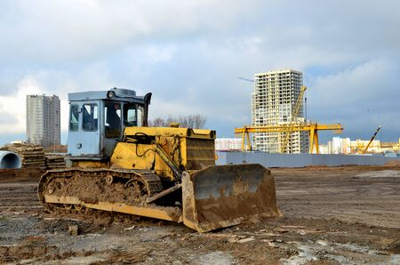 Bulldozer during of large construction jobs at building site.  Crawler tractor dozer for earth-moving. Land clearing, grading, pool excavation, utility trenching and foundation digging. Zdjęcie Seryjne