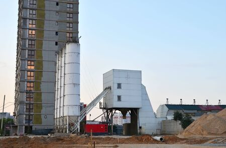 Ready mix stationary concrete batching plant on construction site. Producing сoncrete and portland cement mortar for construction industry. Constructing a new building