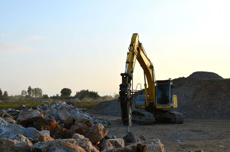 Crawler excavator with hydraulic breaker hammer for the destruction of concrete and hard rock at the construction site or quarry.  Jackhammer using without blasting method. Hard rock demolition 版權商用圖片