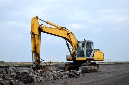 Large tracked excavator with hydraulic hammer breaks asphalt at a construction site on the background sunset. Breaking rock and reinforced Concrete. Road repair, asphalt replacement. Demolition tools