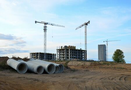The drainage pipes at the large scale construction site against tower cranes and blue sky. Construction of high-rise buildings. Installation of water main, sanitary sewer, storm drain systems.