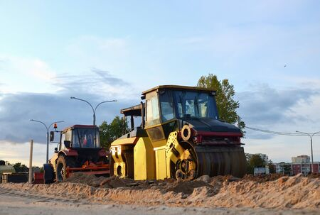 Road roller working at construction site during asphalt road repair. Paving roller machine on paving works. 写真素材