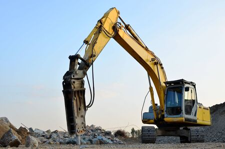 Crawler excavator with hydraulic breaker hammer for the destruction of concrete and hard rock at the construction site or quarry.  Jackhammer using without blasting method. Hard rock demolition 新聞圖片