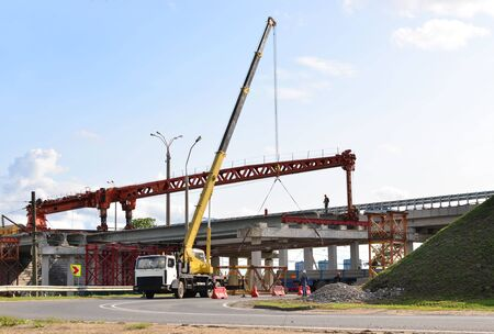 Truck crane working on a construction site. Loading cargo on a truck tractor. Reconstruction and construction of the automobile bridge, replacement of concrete slabs. Workers control work and loading Фото со стока
