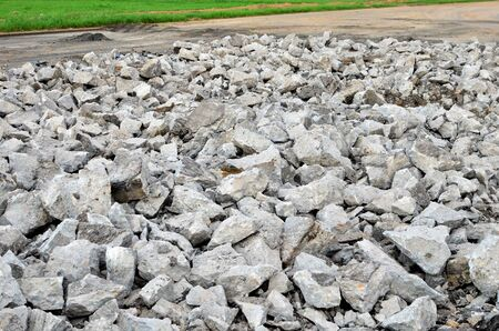 Broken pieces of asphalt at a construction site. Recycling and reuse crushed concrete rubble, asphalt, building material, blocks. Crushed сoncrete Background. Road repair, replacement of old pavement