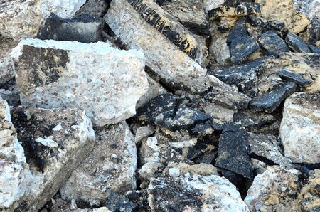 Broken pieces of asphalt at a construction site. Recycling and reuse crushed concrete rubble, asphalt, building material, blocks. Crushed �oncrete Background. Road repair, replacement of old pavement Banque d'images - 140989436