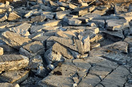 Broken pieces of asphalt at a construction site. Recycling and reuse crushed concrete rubble, asphalt, building material, blocks. Crushed �oncrete Background. Road repair, replacement of old pavement Banque d'images - 140989672