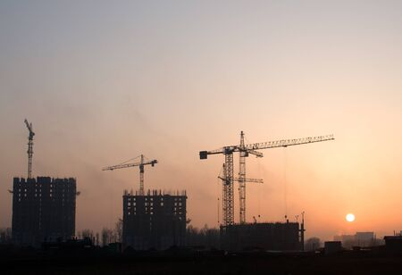 Silhouettes of tower cranes constructing a new residential building at a construction site against sunset background. Renovation program, development, concept of the buildings industry.