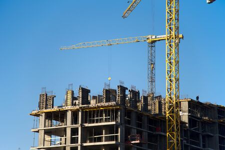 Tower cranes constructing a new residential building at a construction site against blue sky. Renovation program, development, concept of the buildings industry. Stockfoto