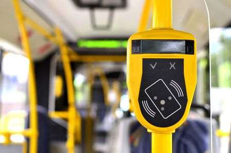 Automatic validator for reading and scanning ticket, cards and bank cards in public transport to pay for riding. Wireless contactless cashless payments, rfid nfc.
