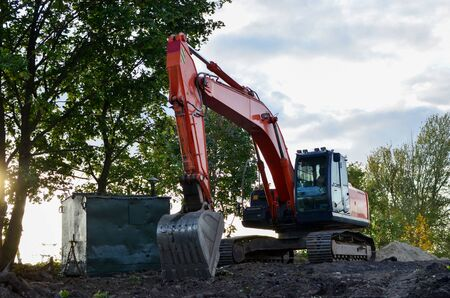 Bucked tracked excavator digs ground at a construction site for installing concrete storm pipes. Backhoe the digging pipeline ditch. Commercial and Public Civil Work Contracting, trenching, tamps soil Stock Photo