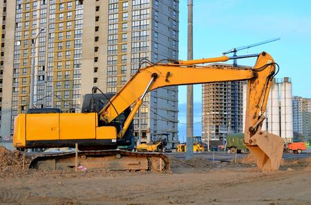 Excavator working at a construction site. Backhoe dig the ground for the foundation, laying storm sewer pipes. Installation of water main systems. Heavy construction equipment for road construction.