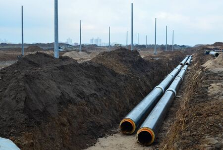 Laying underground storm sewers at a construction site. Groundwater system for new residential buildings in the city. Installation of water main, sanitary sewer, storm drain systems in city. Stock fotó