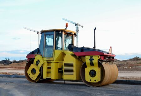 Road roller working at construction site during asphalt road repair. Paving roller machine on paving works.