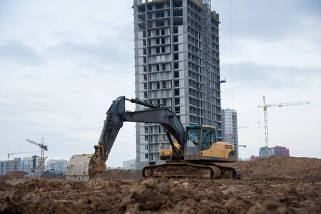 Excavator at building under construction. Backhoe digs the ground for the foundation and for laying sewer pipes. Renovation program. Buildings industry background