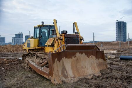 Bulldozer during land clearing and foundation digging at large construction site.  Crawler tractor with bucket for pool excavation and utility trenching. Dozer, Earth-moving equipment.