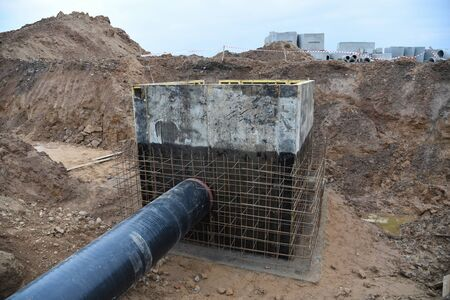 Laying of underground storm sewer pipes in ditch. Installation of water main and sanitary sewer at the construction site. Formwork solutions for reinforced construction and framed superstructure.