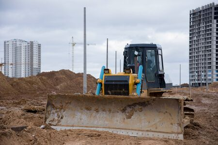 Dozer during land clearing and foundation digging against tower cranes at large construction site. Bulldozer with bucket for pool excavation and utility trenching. Earthmoving works & heavy machinery Zdjęcie Seryjne