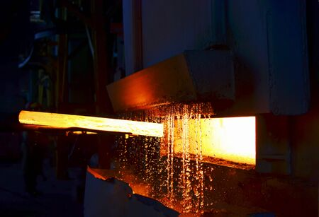 Steel quenching at high temperature in industrial furnace at the workshop of a forge plant. Process of cooling, heat treatmen. Blacksmith and metallurgical industry, steelmaking, hot rolling mill Banque d'images