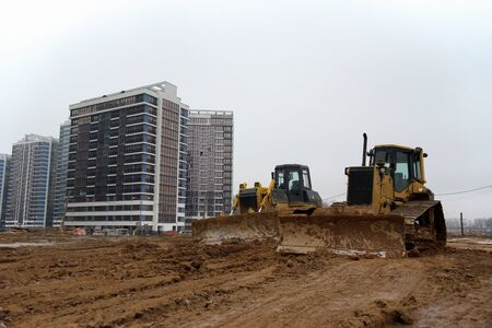 Group of dozers with buckets at construction site. Bulldozer during land clearing, grading, pool excavation, utility trenching and foundation digging. Small roughness sharpness, possible granularity Zdjęcie Seryjne
