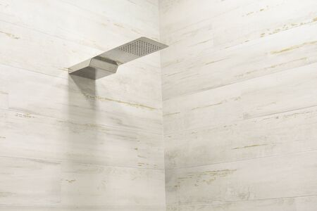 Modern chrome shower head in the bathroom on a background of white tiles on wall. Luxury light themed background for interior and design. Small sharpness