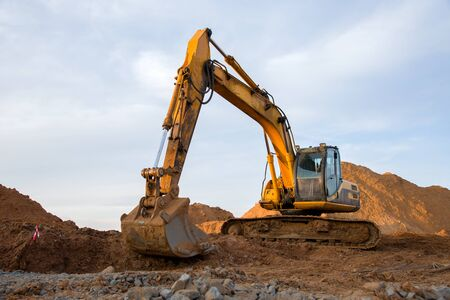 Track-type excavator during earthmoving work at open-pit mining. Loader machine with bucket in sand quarry. Backhoe digging the ground for the foundation and for laying sewer pipes district heating