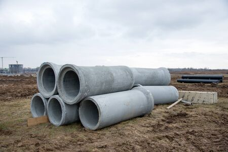 Concrete sewer pipes for laying an external sewage system at a construction site. Sanitary drainage system for a multi-story building. Civil infrastructure pipe, water lines and storm sewers Foto de archivo