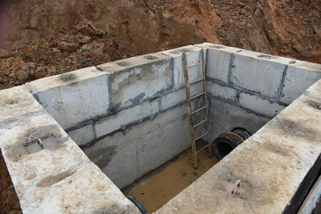 Valve pit for underground piping networks on construction site. Concrete manhole rings and valve chamber sewage pumping stations. Construct stormwater and underground utilities. Instaling sewers pipes