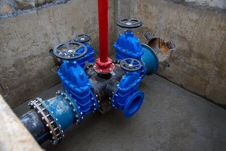 Gate valves in valve pit of the underground piping networks. Laying water system pipeline at construction site. Water supply pipeline, pipes in trench. Sewage pumping stations, stormwater, utilities
